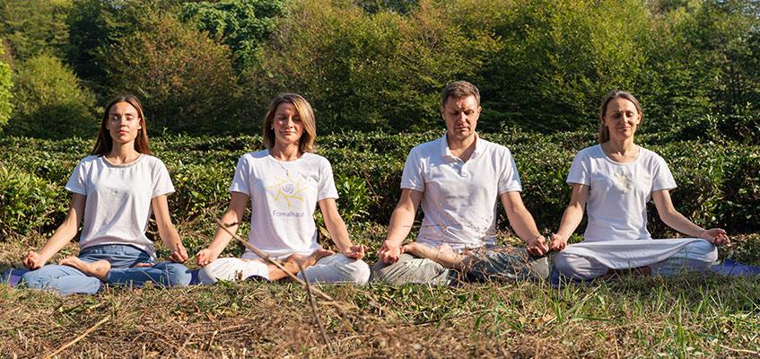 Люди сидят на траве и медитируют